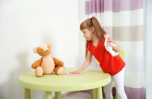 child cleaning table with stuffed animal